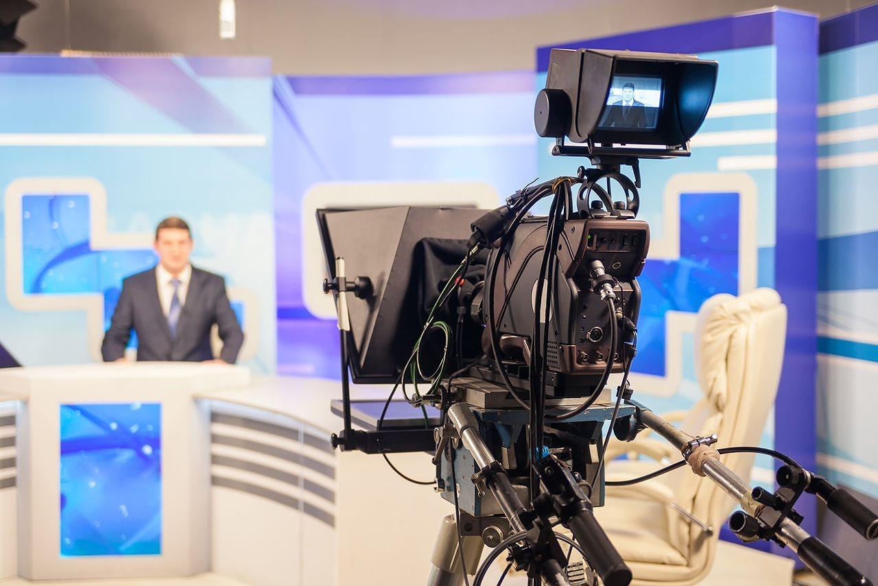 スタジオのカメラとニュースキャスター