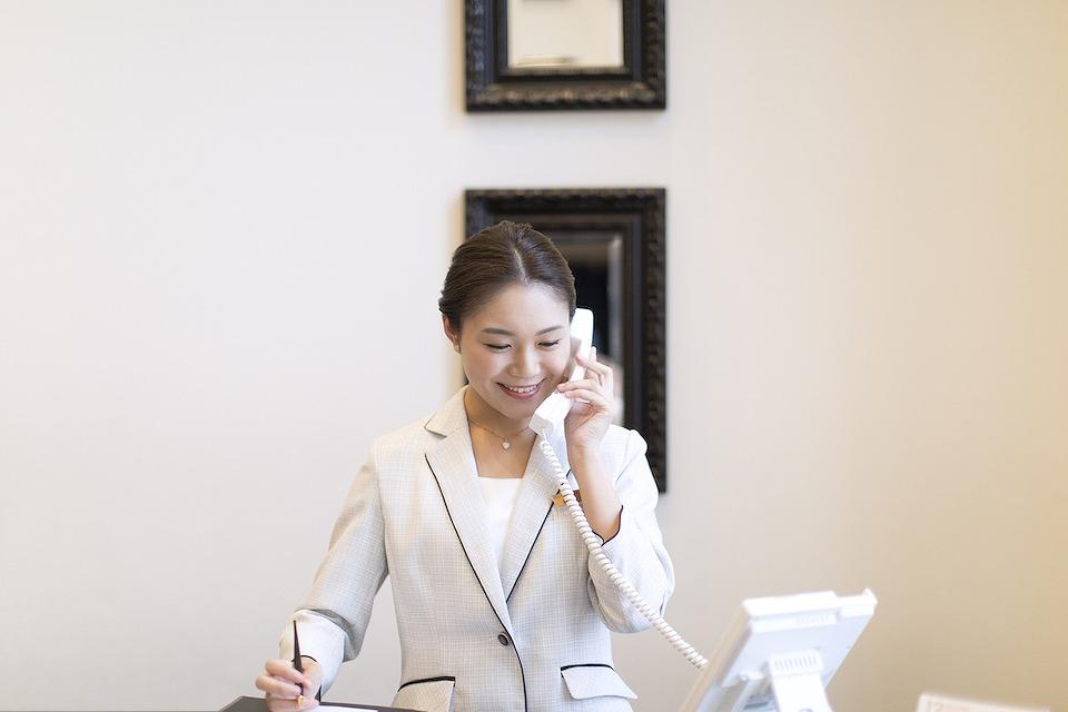 受付の電話に出る女性