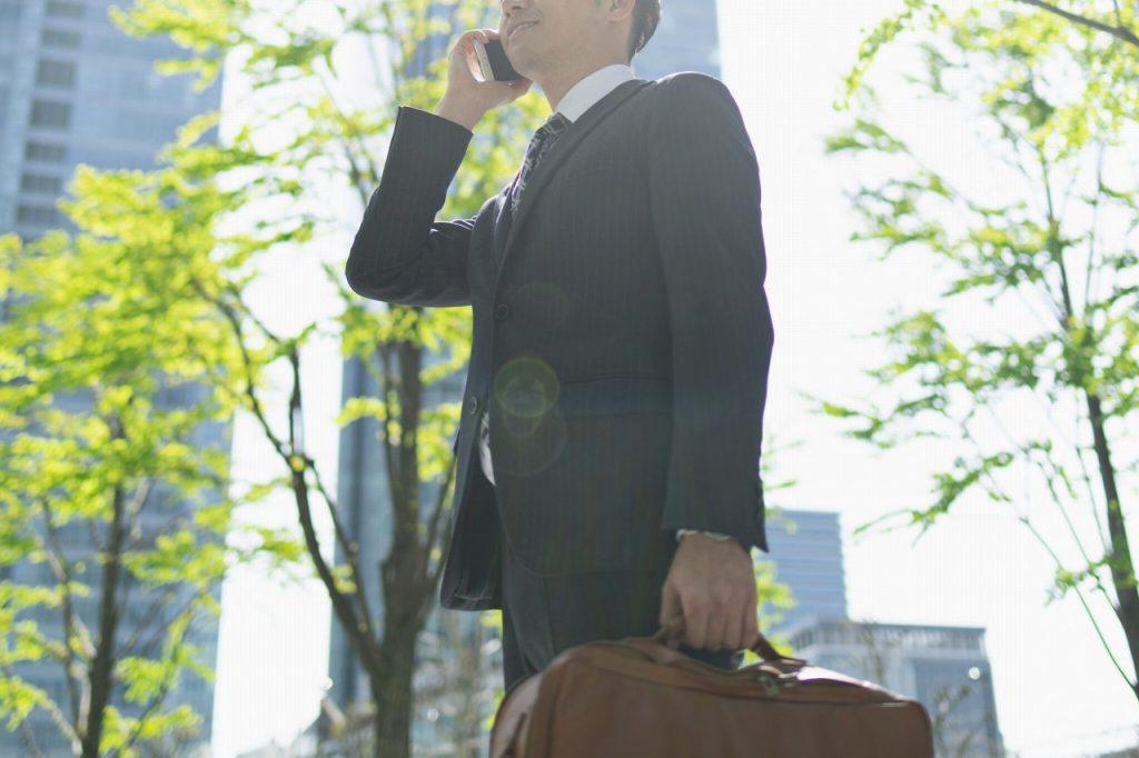 外出中に電話で話すスーツの営業マン