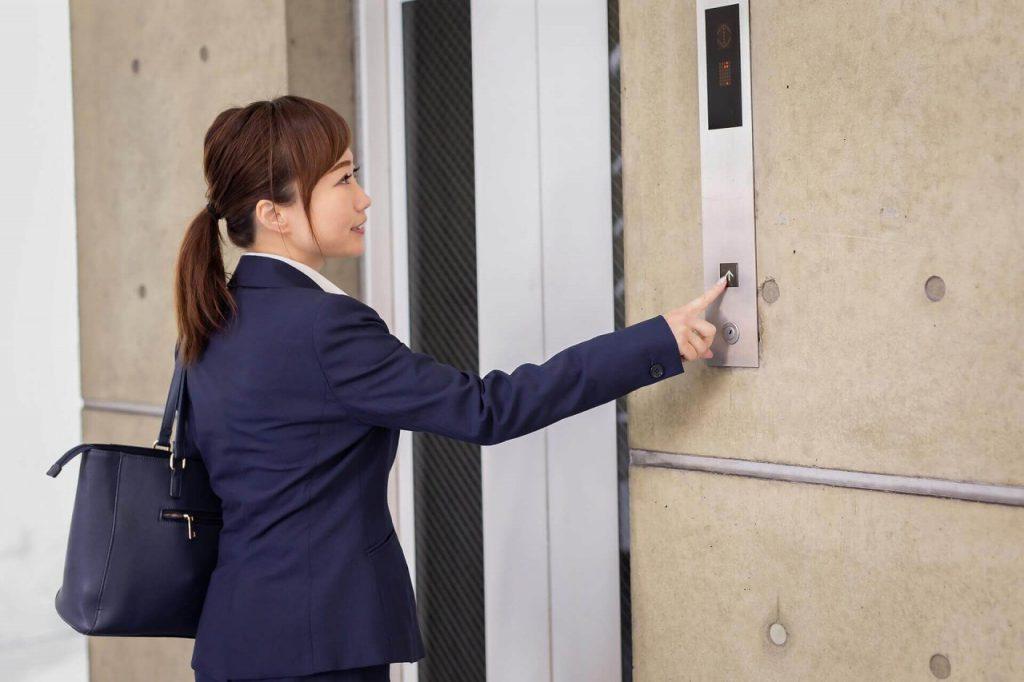 エレベーターのボタンを押す営業女性