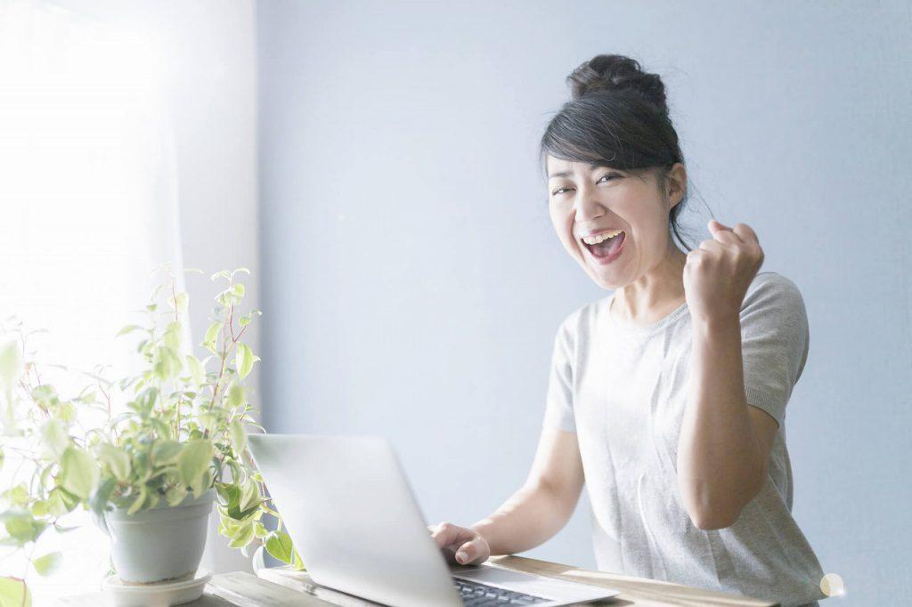 パソコン前でガッツポーズして喜ぶ女性