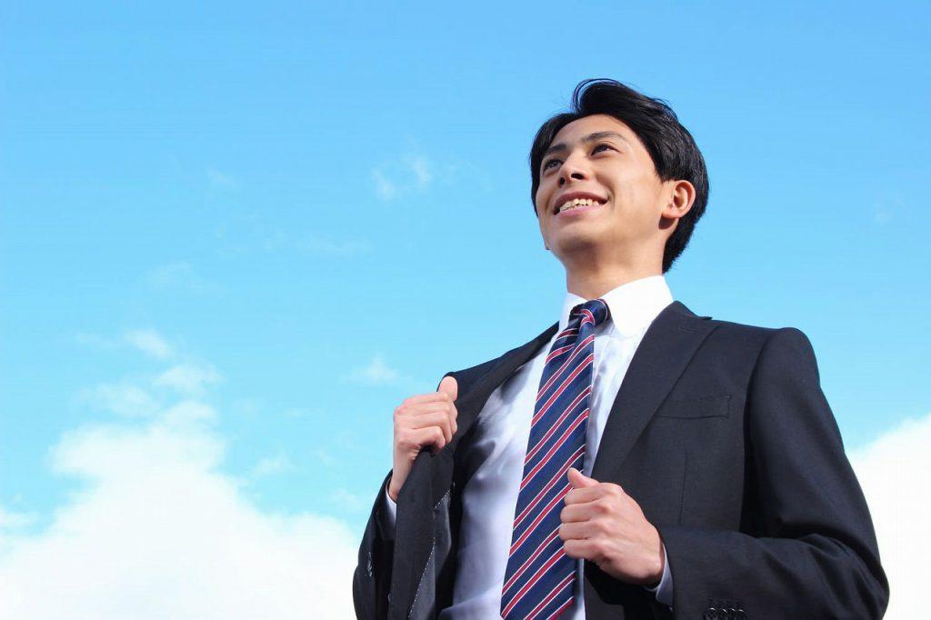 晴れた空と爽やかな営業マン男性