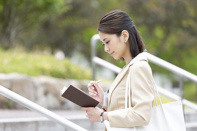 外出先で手帳を確認する営業女性
