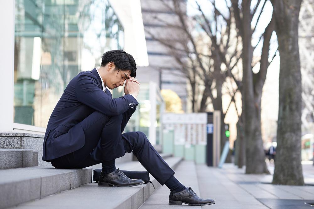 階段に座って悩みを抱えているスーツ男性
