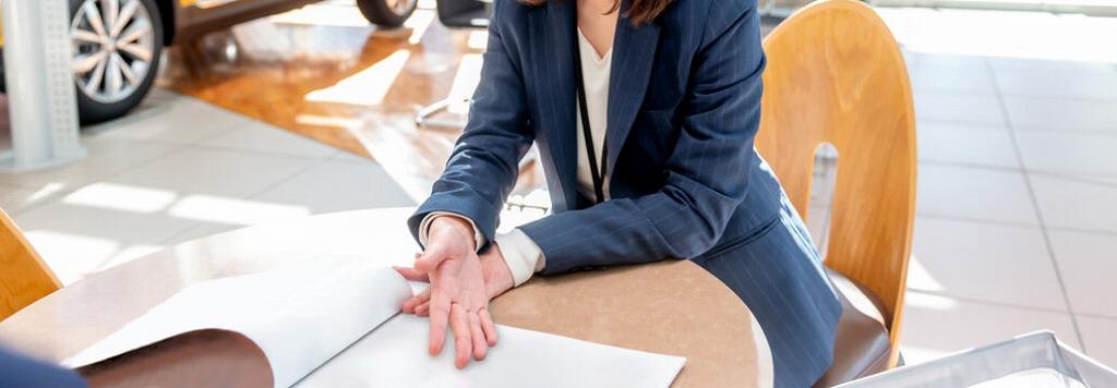営業資料と説明する女性の手元